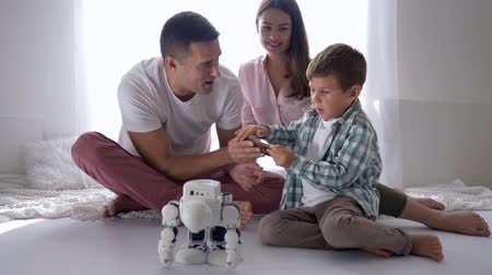 controlli : educational toys, modern child plays automated robot on remote control of smartphone with mum and dad sitting on floor at room