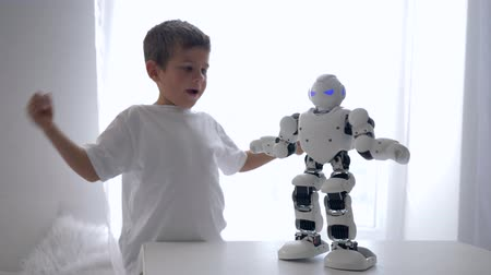 petite : educational toys, cute little boy repeats movements of robot with artificial intelligence close-up in bright room
