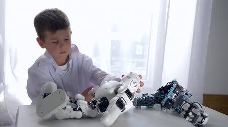 ремонт : children and modern technology, intelligent boy repairs robot toy with Artificial Intelligence in bright studio Стоковые видеозаписи