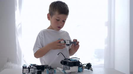 functionality : curious modern child assembles robot piece with artificial intelligence closeup in bright room at home