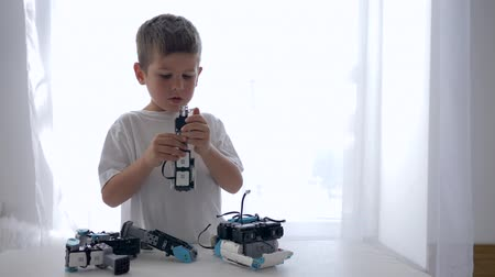 functionality : cute kid assembling of robots parts with artificial intelligence closeup in bright room at home Stock Footage