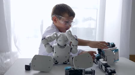 functionality : engineer child repairs smart robot with Artificial Intelligence in bright room