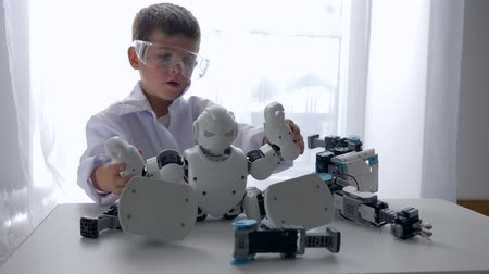 монтаж : innovation technology, little engineer boy assembling Humanoid robot with Artificial Intelligence indoors