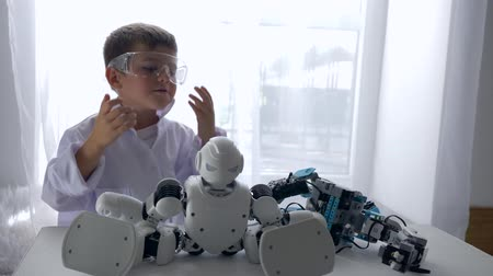 монтаж : modern childhood, curious kid mounting robot toy with Artificial Intelligence in bright laboratory