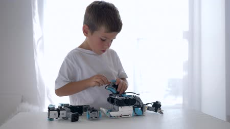 functionality : skillful kid mounting of robots detail with artificial intelligence closeup in bright room at home Stock Footage