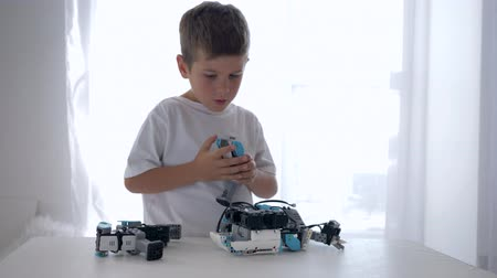 functionality : small modern boy repairs of robots detail with artificial intelligence closeup in bright room at home