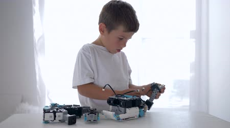 монтаж : smart child boy repairs of robots parts with artificial intelligence closeup in bright room at home Стоковые видеозаписи