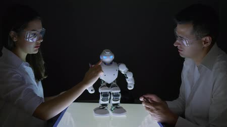 functionality : artificial intelligence, Technical engineers working collaborating on project to build robot in dark workshop