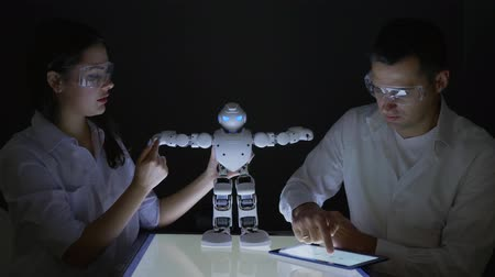 functionality : development of artificial intelligence technologies, engineers scientists studying artificial intelligence of Humanoid robot in modern dark laboratory