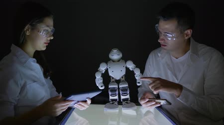 collaborating : engineer female and male start up for robot project of artificial intelligence in dark lab