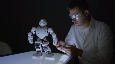 functionality : innovative future, engineers scientists man check functionality of modern robot with artificial intelligence in dark laboratory