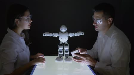 functionality : innovative robotic developments, Electronics engineers collaborating on design of robot in dark lab Stock Footage