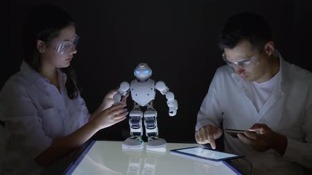 functionality : innovative technologies, Young electronics engineer collaborating on construction of Humanoid robot in dark workshop