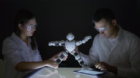 functionality : scientists engineers girl and guy researching functionality of smart robot with artificial intelligence in modern dark lab
