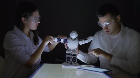 collaborating : scientists engineers woman and man check functionality of smart robot with artificial intelligence in modern dark lab