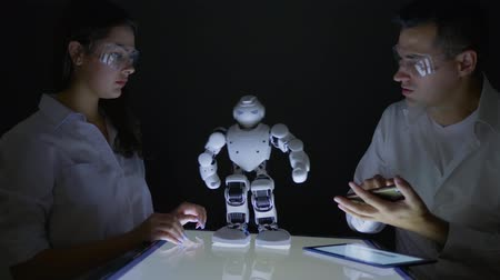 functionality : Smart robotic technology, Electronics engineers collaborating researching abilities of automated robot in modern dark lab