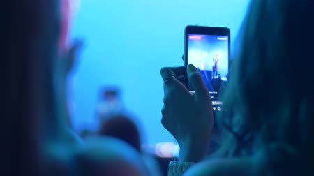 прожектор : admirers with cell phone record video at night concert show close-up on unfocused background in lighting spotlight Стоковые видеозаписи