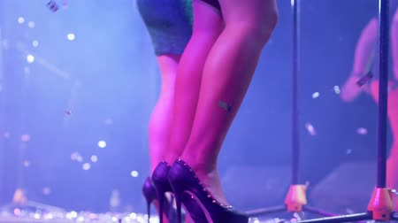 floodlight : legs women singer on high-heeled close-up on concert scene and shiny sparkles flies
