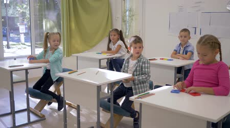 becario : children at school, cute boys and girls sit at desks and raise hands during lesson in classroom in school