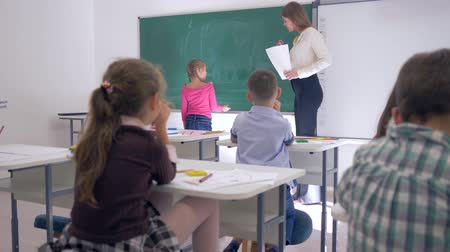 мел : kids in school, children raise their hands to answer teachers question, schoolgirl goes to blackboard to write a simple example Стоковые видеозаписи