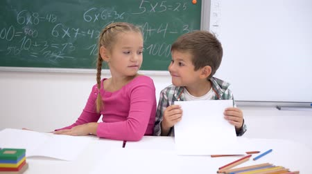 pigtailler : classmates children hugging and smiling sitting at the desk on the background of blackboard in the classroom at school