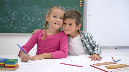 pigtailler : school love, classmates write during lesson at table and then look at the camera and smile on background of blackboard
