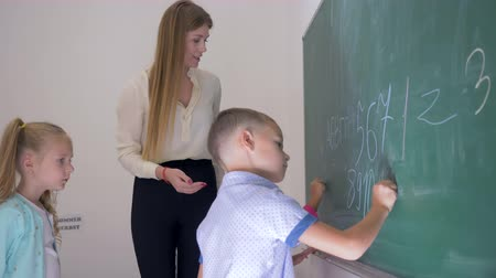 мел : educator help child pupils with chalk in their hands write letters and numbers on the blackboard at the lesson in school