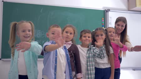feliz : group of elementary school children with a young teacher waving hands on background of blackboard in classroom
