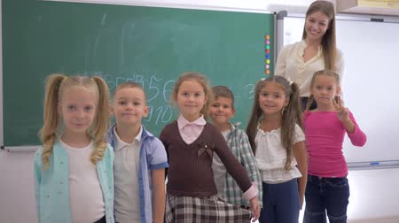 elsődleges : group of primary school children with young educator are smiling and look at the camera on background of blackboard Stock mozgókép