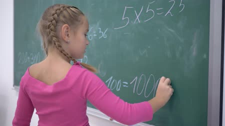 elsődleges : happy schoolgirl with chalk solves examples on mathematics on the school green blackboard during a lesson in class, primary education