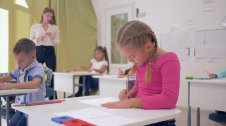 косички : little schoolgirl sitting behind school desk during drawing lesson in the light classroom on background of classmates and a young teacher
