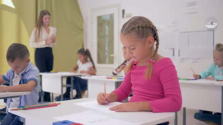 ifjabb : portrait of schoolgirl on drawing lesson in the light classroom sitting behind desk on background of classmates and young teacher