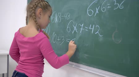 příklad : primary education, schoolgirl with chalk solves examples on mathematics on the school green blackboard in class