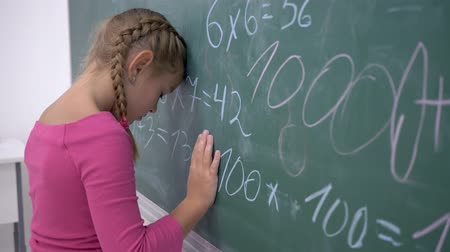 pigtailler : school education, upset female pupil standing near blackboard with mathematics examples in class