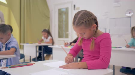pigtailler : schoolgirl draws with pencils on paper and then looks at the camera with a smile at the drawing lesson in a light classroom Stok Video