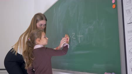 мел : schoolgirl with piece of chalk writes an example on the blackboard with the help of a female teacher at the math lesson