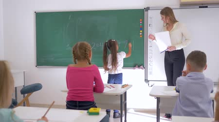 мел : schoolgirl writes an simple example on the chalkboard near educator on math lesson, primary education