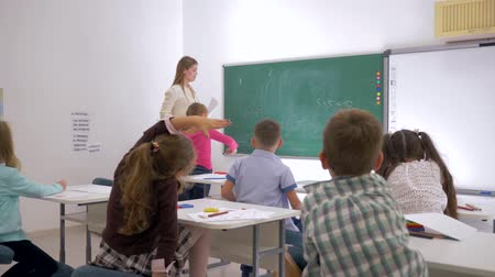 uczennica : teacher stands at front of class near blackboard and asks pupils a question to which they raise their hands Wideo