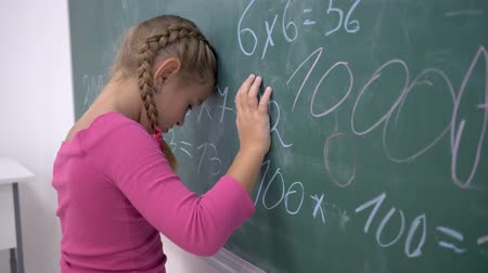 pigtailler : unhappy schoolgirl near blackboard with examples on mathematics in elementary school class