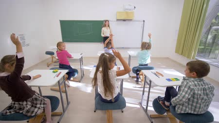 scholar : group of schoolkids raise hands to answer at lesson while sitting at desk in front of teacher to board in elementary school class Stock Footage