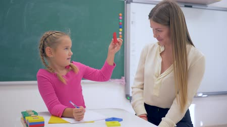 becario : Individual education, Experienced tutor teaching smart girl at table near blackboard in classroom of Primary School Archivo de Video