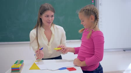 becario : portrait of happy professional teacher female with smart schoolkid girl with plastic figures in hand near board in classroom of elementary school