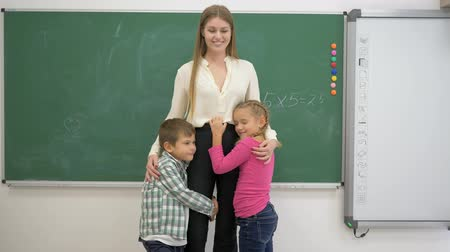 scholar : portrait of smiling classroom teacher hugging with learners children near blackboard in school