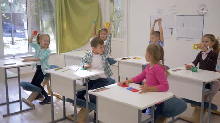 becario : preschool education, smart happy kids lift up geometric shapes in hand during lesson in classroom