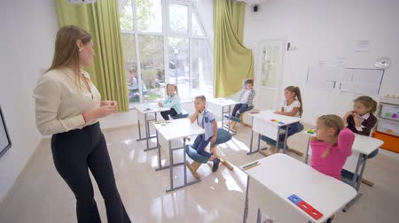 becario : teacher female interacts with little cute children schoolchild at desks during education lesson in classroom at Junior School
