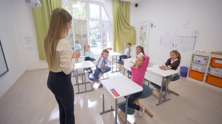 scholar : young educator female talks to cute little scholars children at desks during teaching lesson in classroom at Primary School Stock Footage