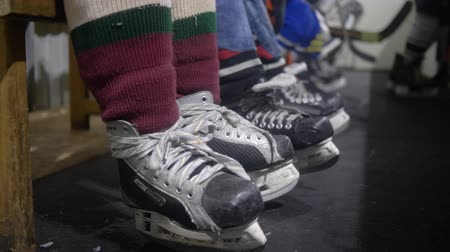 minor : KHERSON, UKRAINE - OCTOBER 28, 2018: legs of hockey players in skates, little sportsmans sits on bench before the game near border of ice arena Stock Footage