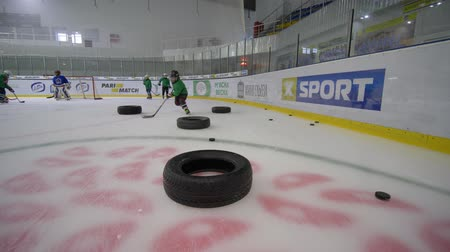 hokej : KHERSON, UKRAINE - OCTOBER 28, 2018: play hockey, children on skates training with pucks around tyres on the ice arena in slow motion
