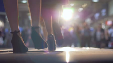 semana de moda : KHERSON, UKRAINE - OCTOBER 20, 2018: fashion industry, models defiles on the podium in high-heeled shoes on background of illumination and blurred audience