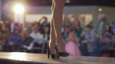 semana de moda : fashion show, model legs goes to the podium in high-heeled shoes in short dress on background of light and audience